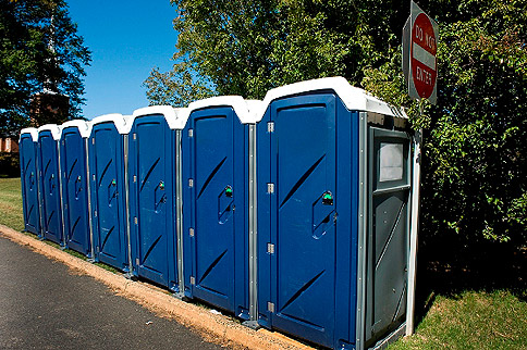 Row of portable toilets next to a curb