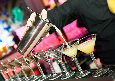 Row of cocktails being poured out on a bar