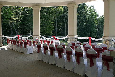 White and red wedding chair covers in outside venue